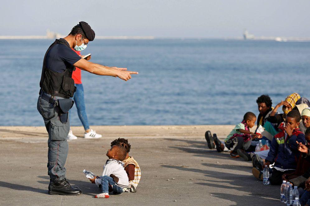 Foto: Un policía italiano habla con menores inmigrantes que acaban de desembarcar en Augusta, Sicilia. (Reuters)