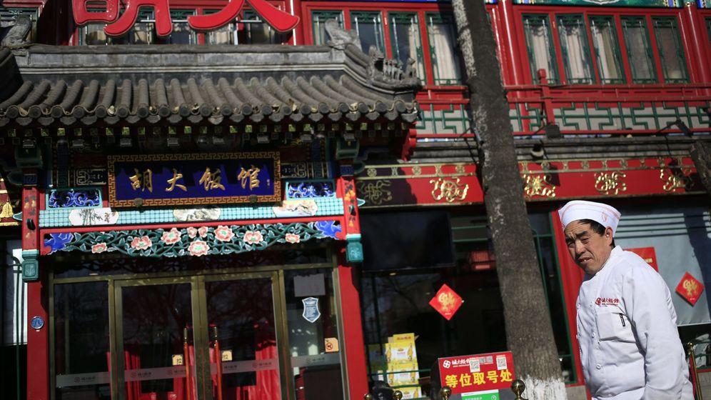 Foto: Un chef chino pasa delante de un restaurante en Pekín, en enero de 2016 (EFE)