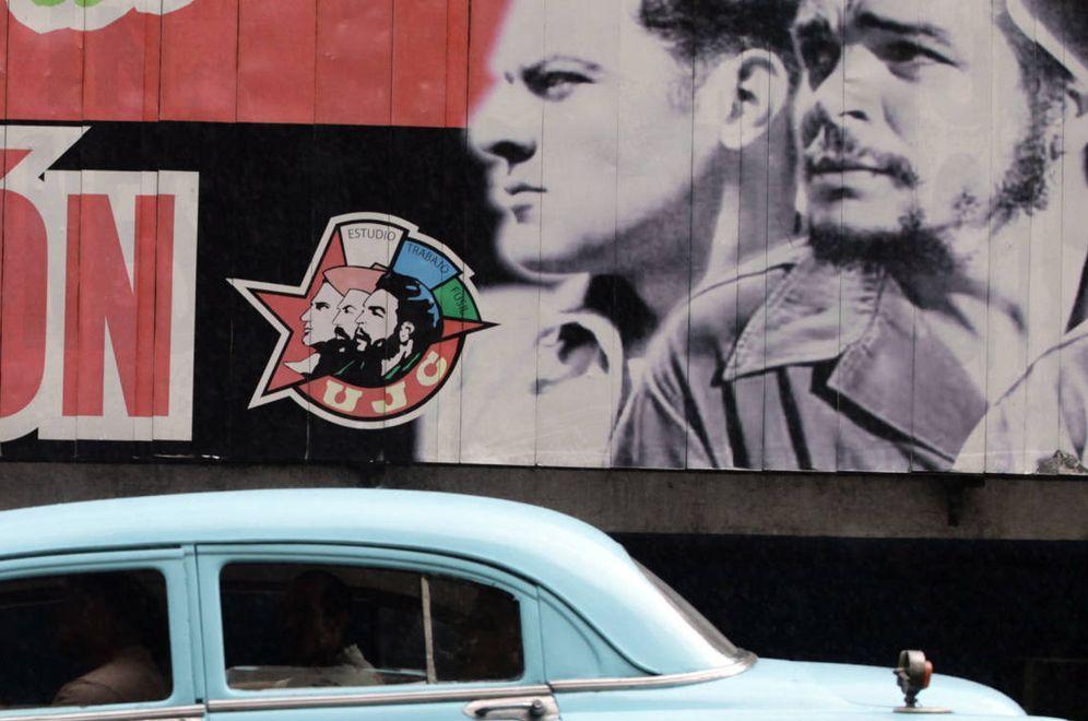 Foto: Un almendrón, uno de los coches fabricados antes de la Revolución, pasa por delante de un cartel revolucionario en La Habana. (Reuters)