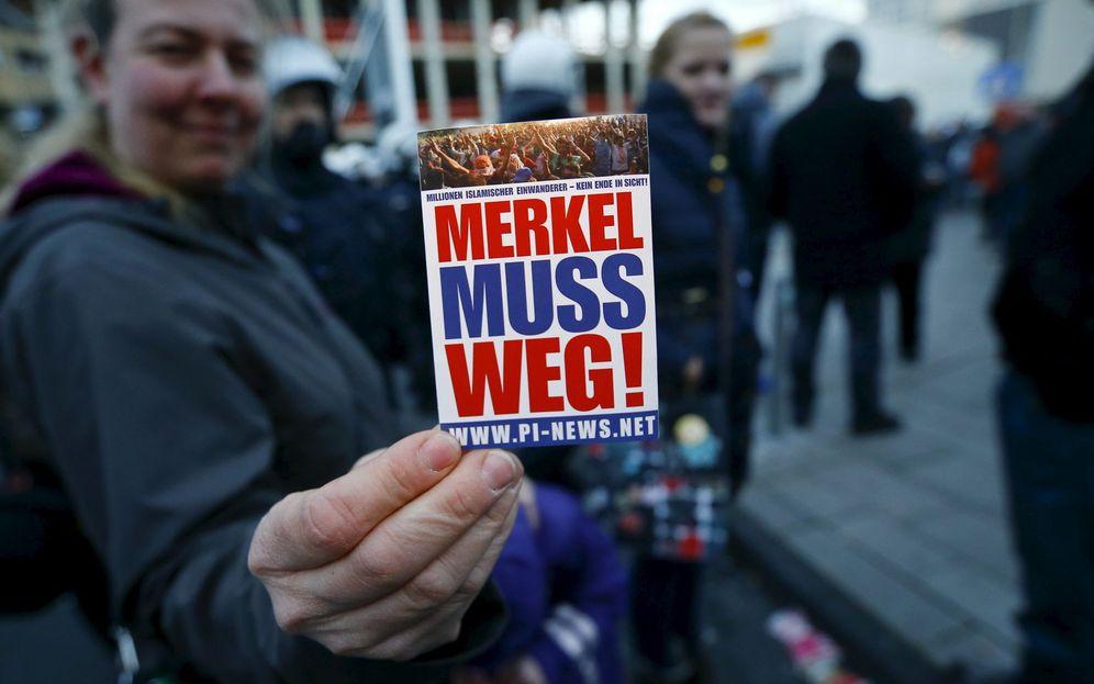 Foto: Seguidores del movimiento Pegida muestran una pegatina que reza 'Merkel debe dimitir', durante una protesta en Colonia, el 9 de enero de 2016. (Reuters)