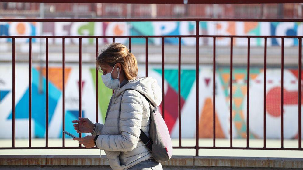 Foto: Una mujer con una máscara pasea delante de un colegio de Madrid cerrado por el coronavirus. (Reuters)