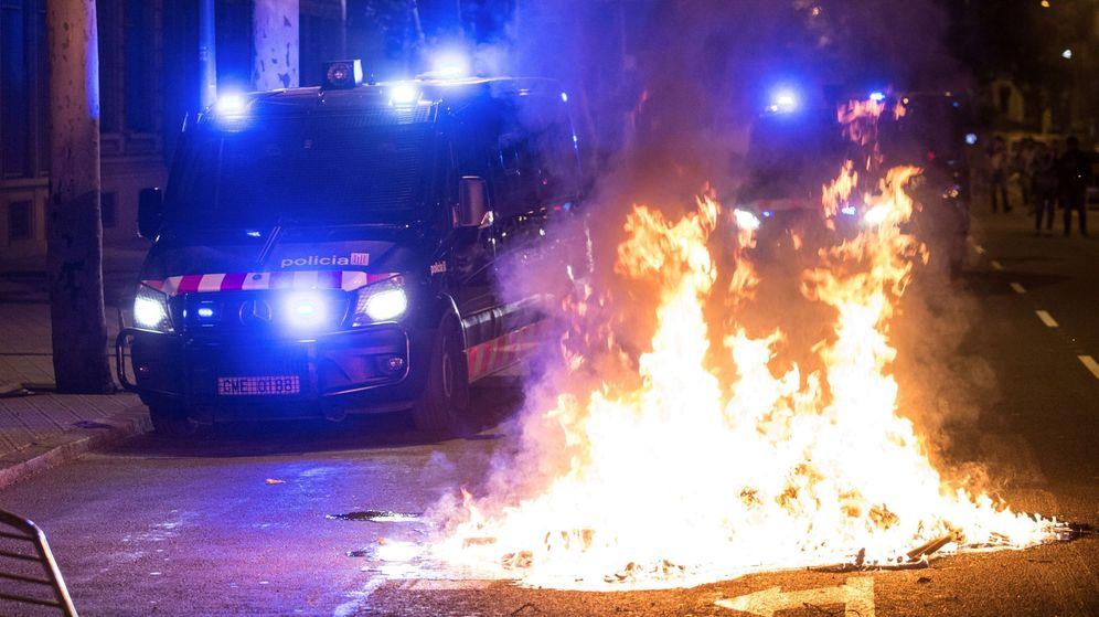 Foto: Un furgón de los Mossos d'Esquadra pasa junto al fuego durante los altercados al finalizar la movilización convocade por la ANC y otras entidades soberanistas. (EFE)