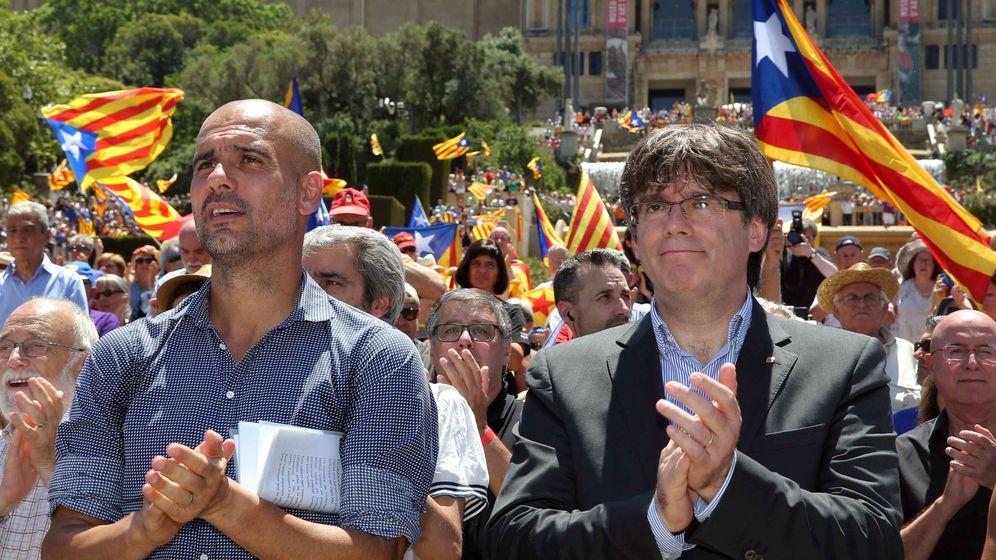 Foto: Carles Puigdemont y Pep Guardiola aplauden al finalizar un acto con el lema 'Referéndum es democracia'. (EFE)
