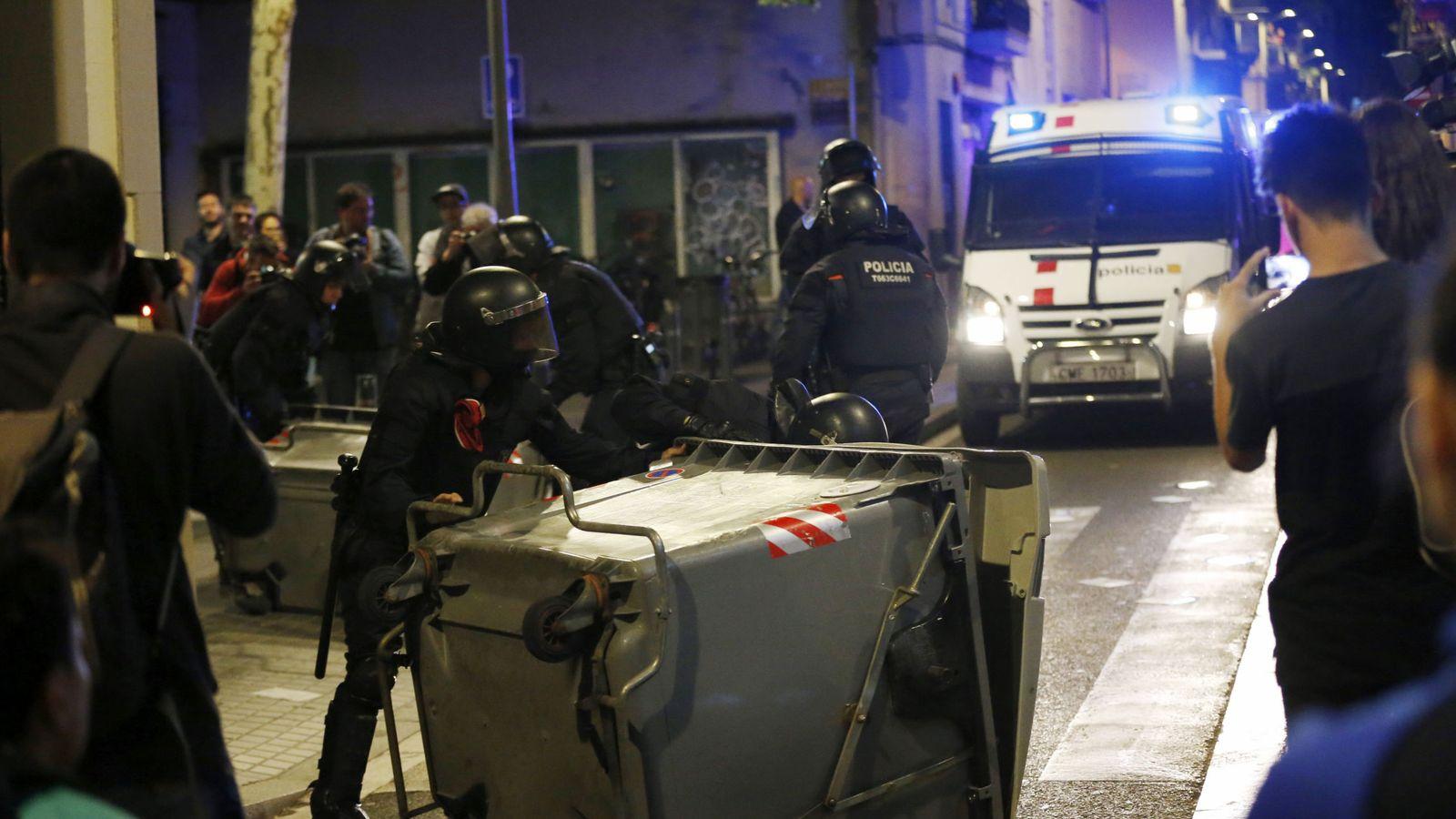 Foto: Varios antidisturbios retiran contenedores volcados en el barrio de Gràcia, en Barcelona. (Efe)