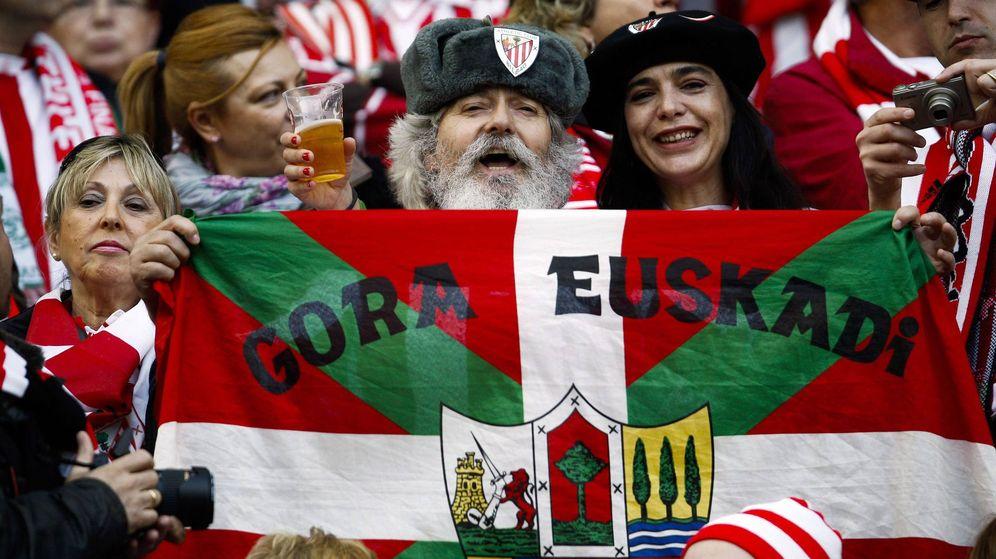 Foto: Un aficionado del Athletic de Bilbao muestra una bandera vasca mientras anima a su equipo antes del inicio del partido. (EFE)
