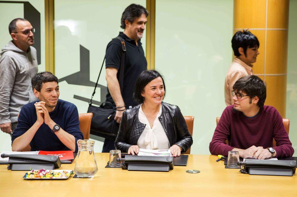 Foto: Representantes de Bildu en la Ponencia de Autogobierno pasan por detrás de los de Podemos. (EFE)