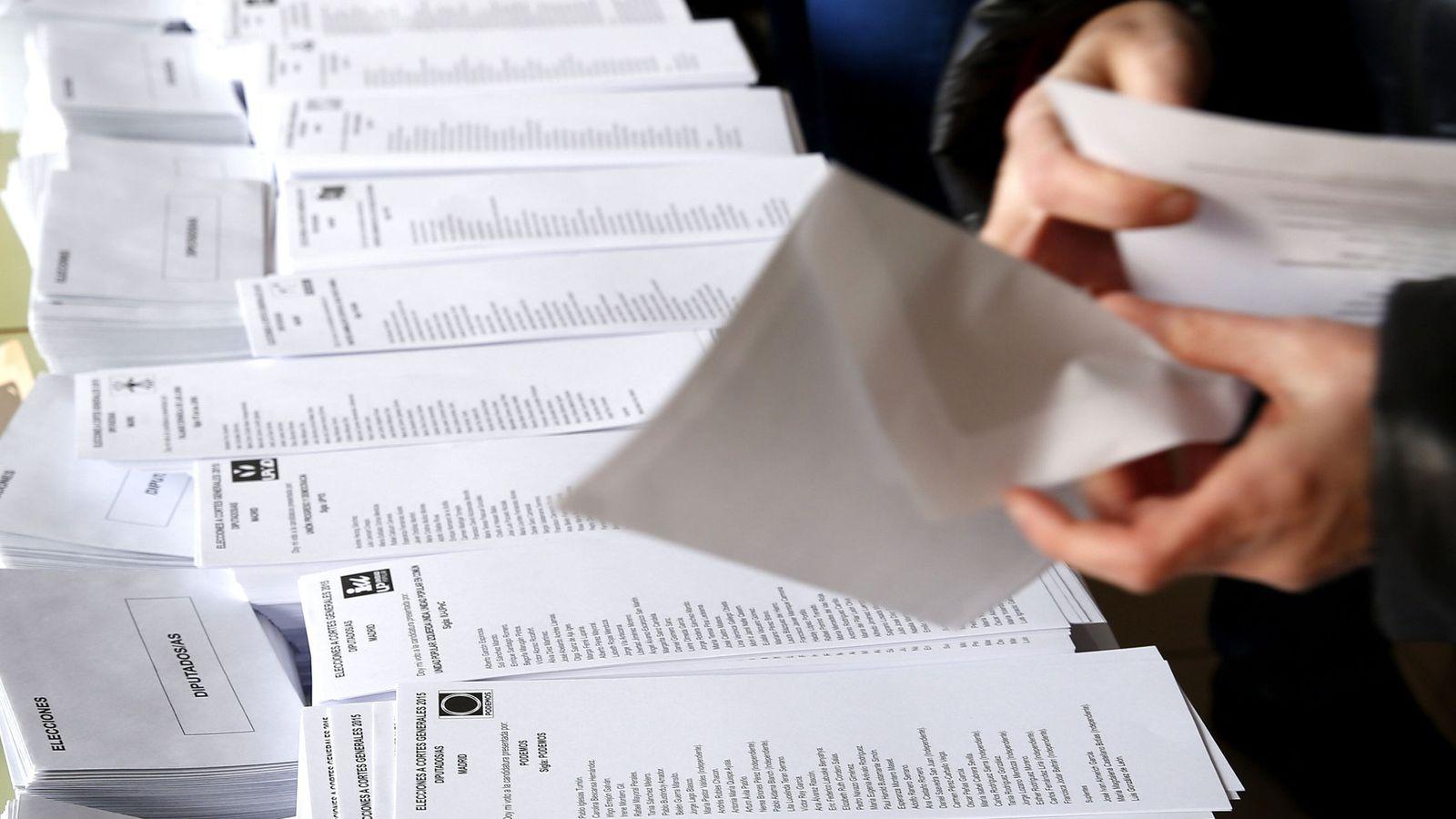 Foto: Una persona selecciona una de las papeletas al Congreso en un colegio electoral en Madrid. (EFE)