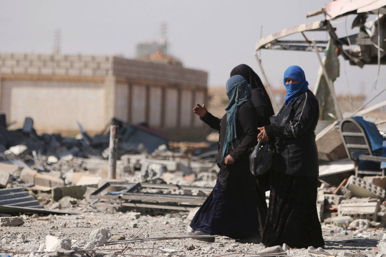 Foto: Dos mujeres sirias caminan entre los escombros de la ciudad de Al-Shadadi, en la provincia siria de Hasaka (Reuters).