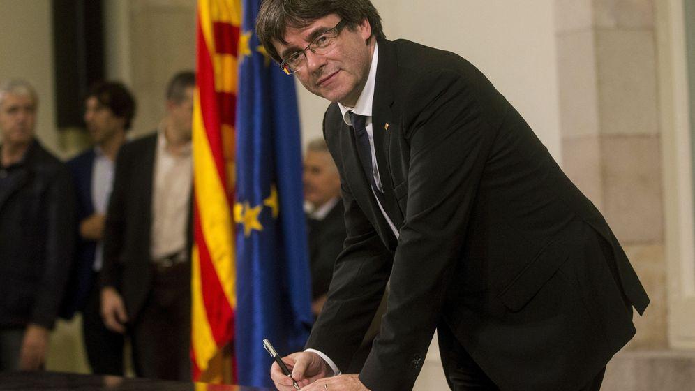 Foto: El presidente de la Generalitat, Carles Puigdemont, firma el documento sobre la Independencia después de comparecer ante el pleno del Parlament para trasladar los resultados de la jornada del 1-O. (EFE)