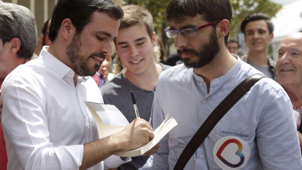 Foto: El candidato de Unidos Podemos Alberto Garzón firma un libro a un simpatizante en Zaragoza. (EFE)