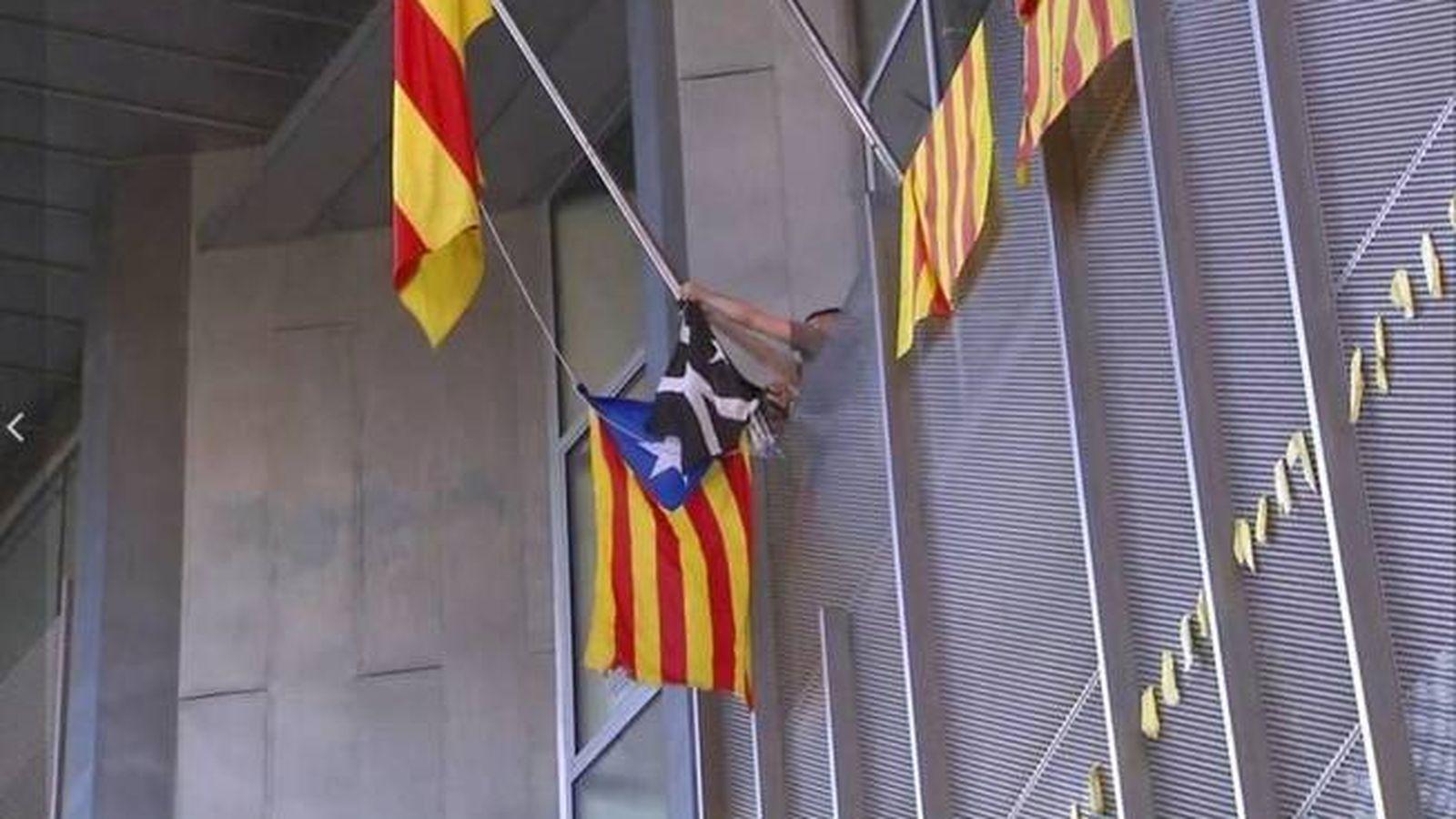 Foto: Miembros de los CDR colocan una bandera negra en la Delegación de la Generalitat en Girona