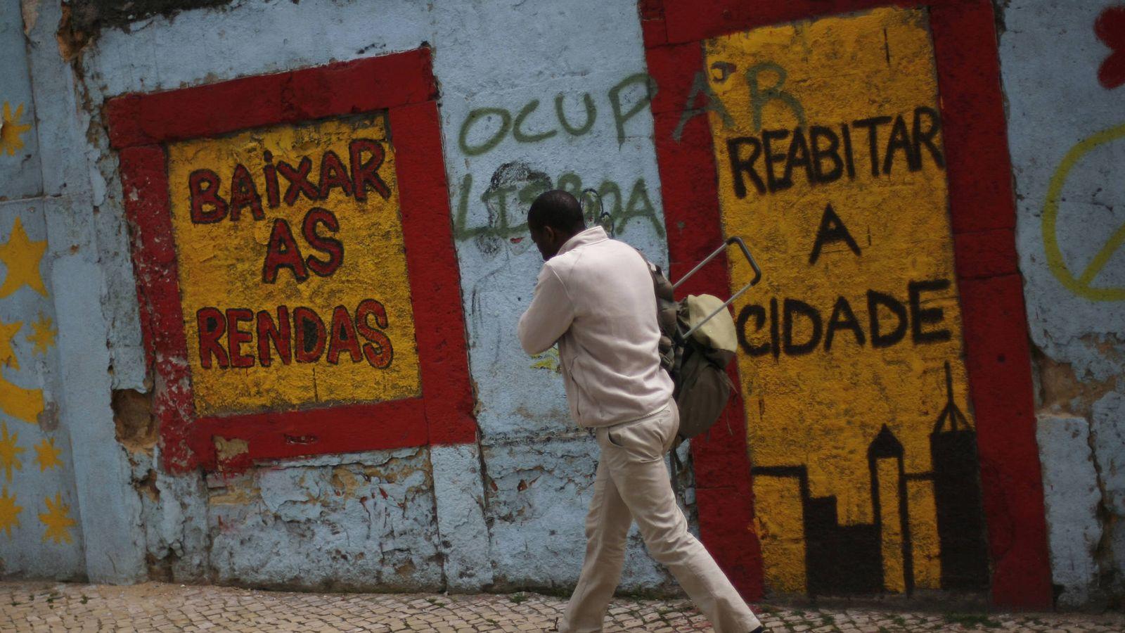 """Foto: Un hombre pasa ante una pintada que pone """"alquileres más bajos"""", en Lisboa. (Reuters)"""