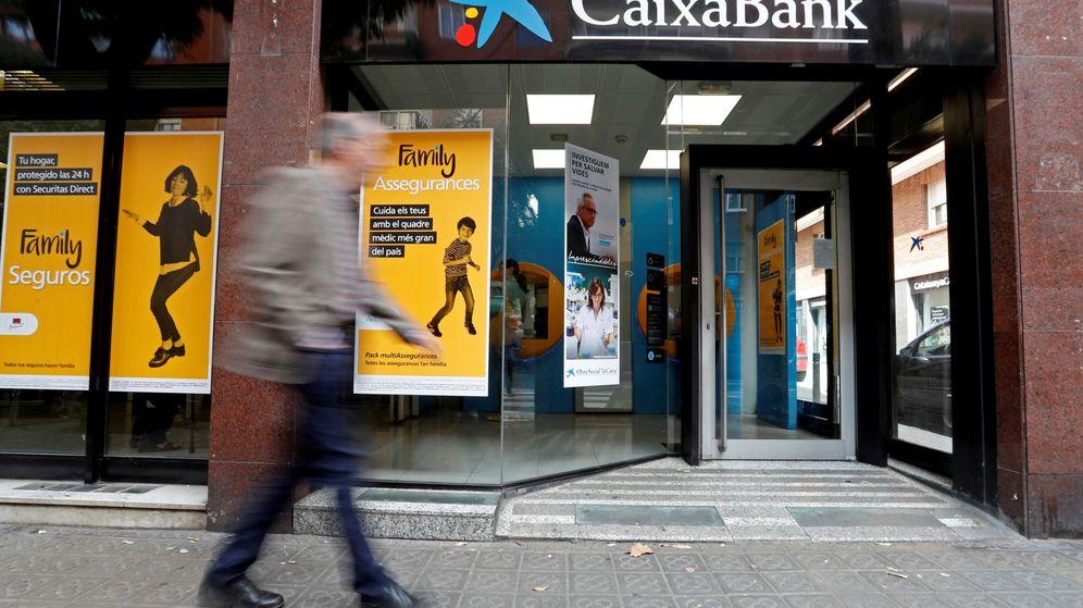 Foto: Un hombre camina frente a una sucursal de CaixaBank. (Reuters)