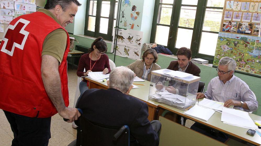 Foto: Voluntarios de la Cruz Roja trasladan a un anciano hasta un colegio electoral de Ciudad Real. (EFE)