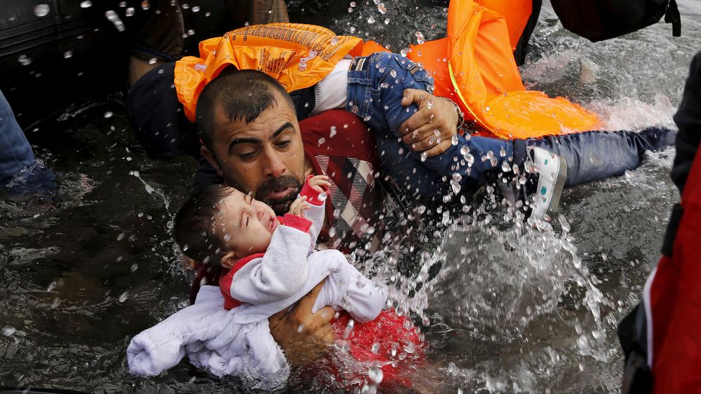 Foto: Un refugiado sirio sostiene a su hijo en su trayecto hasta la isla de Lesbos en 2015. (Reuters)