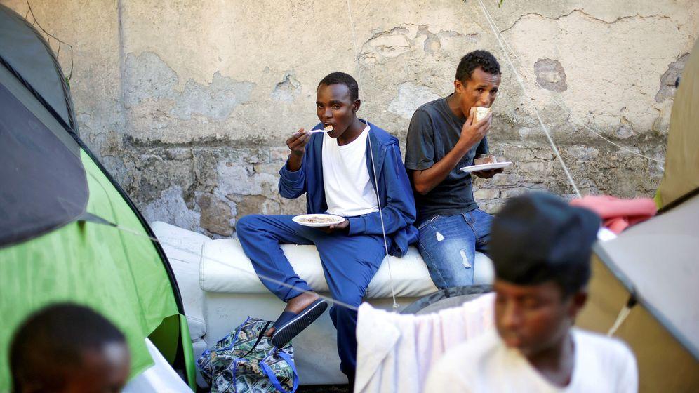 Foto: Un grupo de inmigrantes come alimentos proporcionados por voluntarios en un campamento improvisado en el centro de Roma, en agosto de 2016. (Reuters)