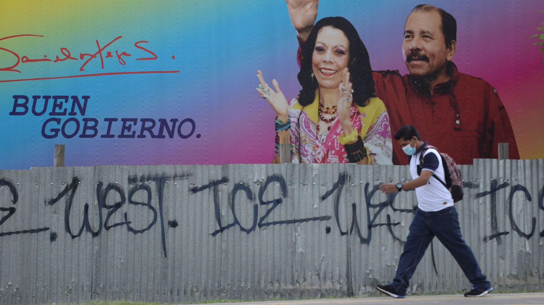 Un hombre camina frente a una pancarta en la que aparecen Rosario Murillo y Daniel Ortega. (Reuters)