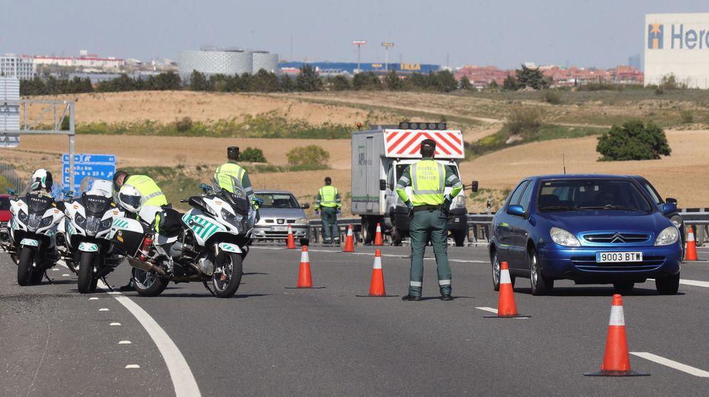 Foto: Agentes de la Guardia Civil realizan un control de vehículos en la autopista A-5 en su salida de Madrid. (EFE)