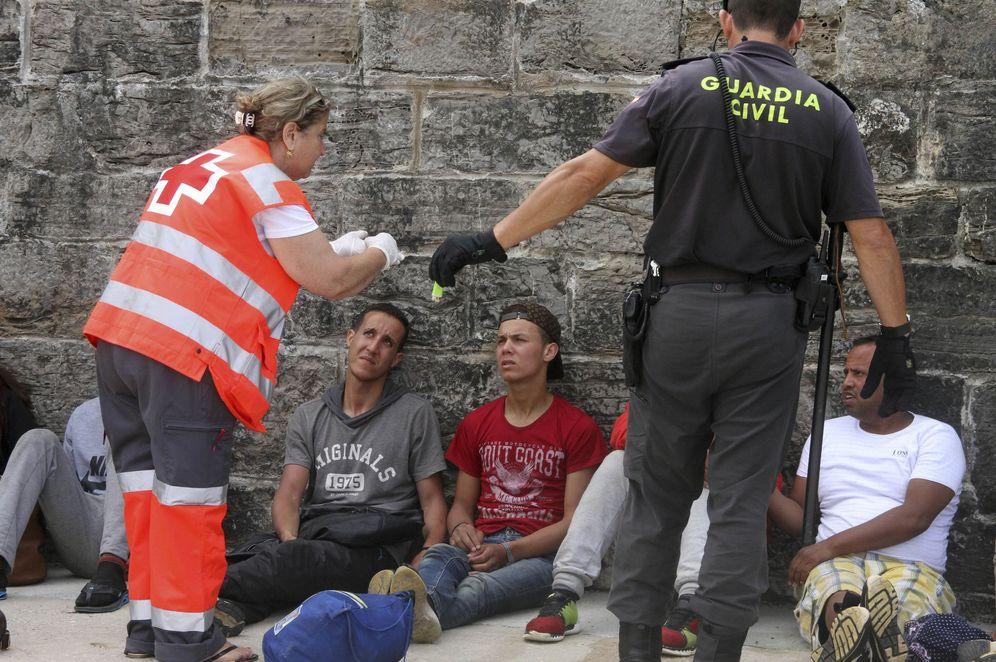 Foto: Agentes de la Guardia Civil y personal de Cruz Roja ayudan a 88 personas rescatadas en tres pateras y llevadas al puerto de Tarifa, el 23 de junio de 2017. (EFE)