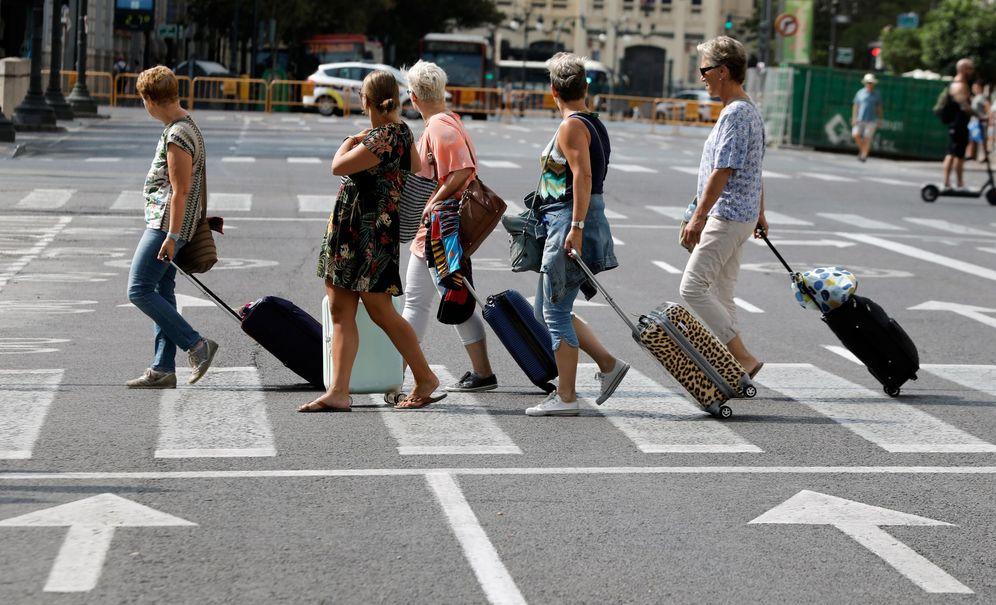 Foto: Varios turistas atraviesan un paso de cebra con sus maletas. (EFE)