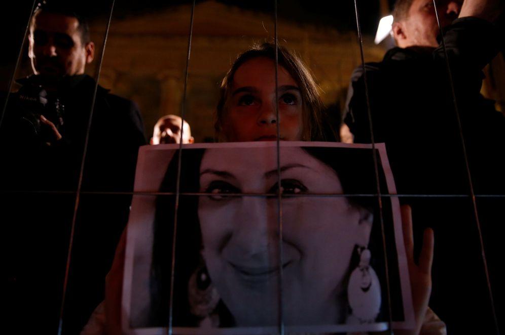 Foto: Una joven sostiene una foto de la periodista Daphne Caruana Galizia durante una vigilia en Valletta, Malta. (Reuters)