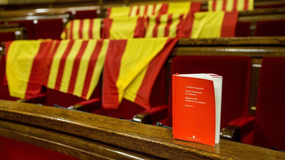 Foto: Ejemplar con la Constitución española, el Estatuto de Cataluña y el Reglamento del Parlment. (EFE)