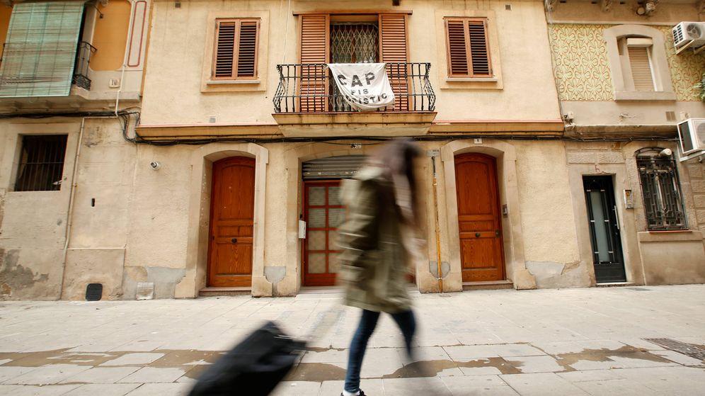 Foto: Una turista arrastra una maleta en la Barceloneta, delante de un cartel que protesta contra la presencia masiva de pisos alquilados. (Reuters)