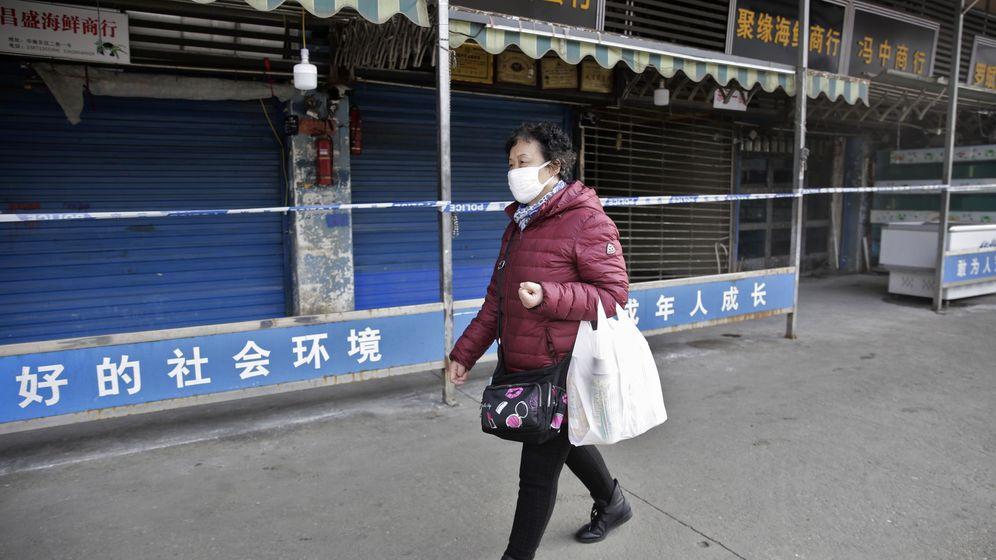 Foto: Una mujer pasea junto al mercado de Huanan Seafood Wholesale Market. (EFE)