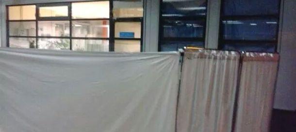 Foto: Biombo con el que taparon la cama del paciente con síntomas de contagio, colocada en la conserjería.