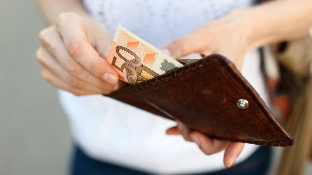 Foto: Una mujer saca dinero de la cartera. (iStock)