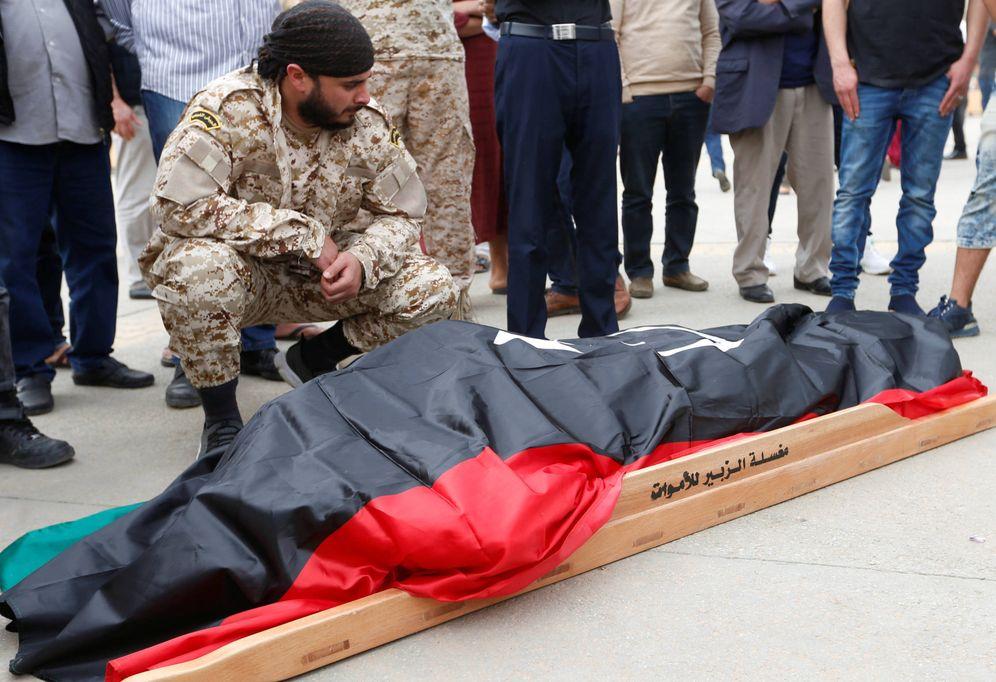 Foto: Un combatiente del Gobierno reconocido por la ONU junto a un compañero caído en los combates, en Trípoli. (Reuters)