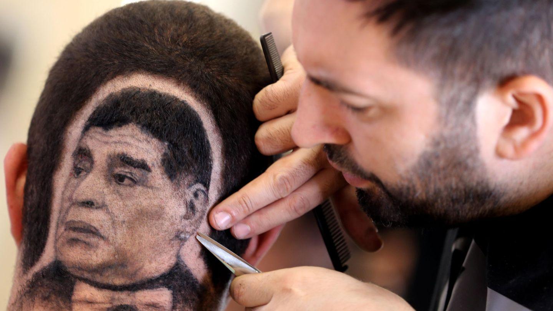 Un joven se corta el pelo con la cara de Maradona en Serbia. (EFE)