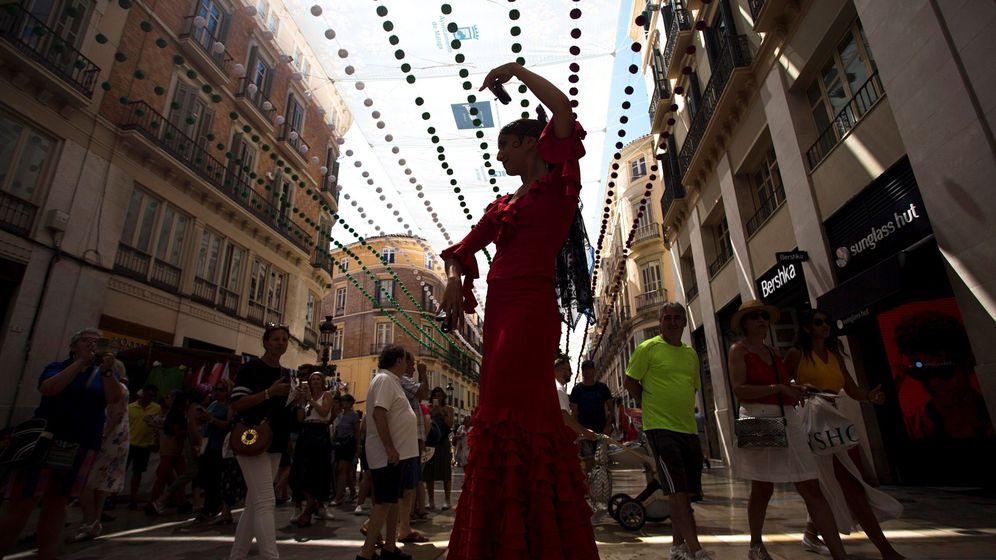 Foto: Una mimo vestida con traje de flamenca actúa en la calle Larios, en la Feria del Centro de Málaga. (EFE)