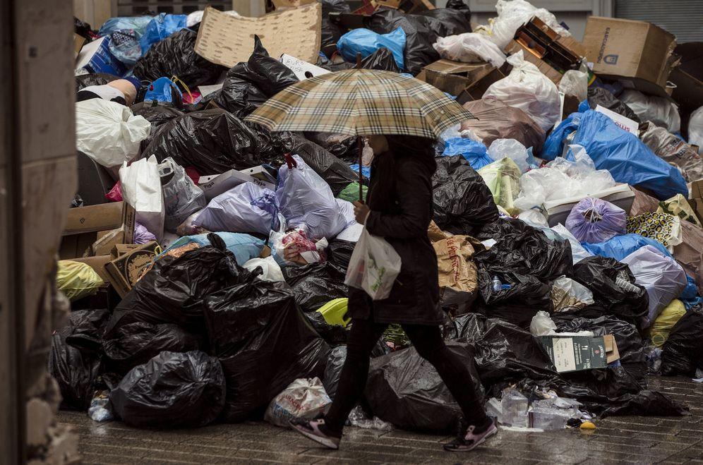 Foto: Una mujer camina junto a la basura acumulada durante la huelga de limpieza en Málaga el pasado año. (EFE)