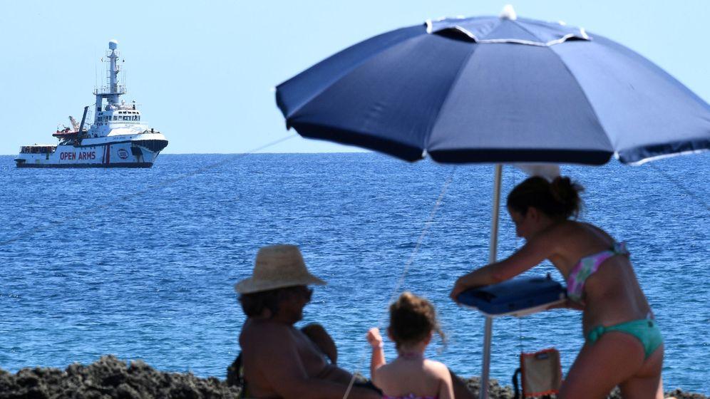 Foto: Bañistas en la playa de Lampedusa con el barco de Open Arms de fondo, a la espera de poder desembarcar. (Reuters)