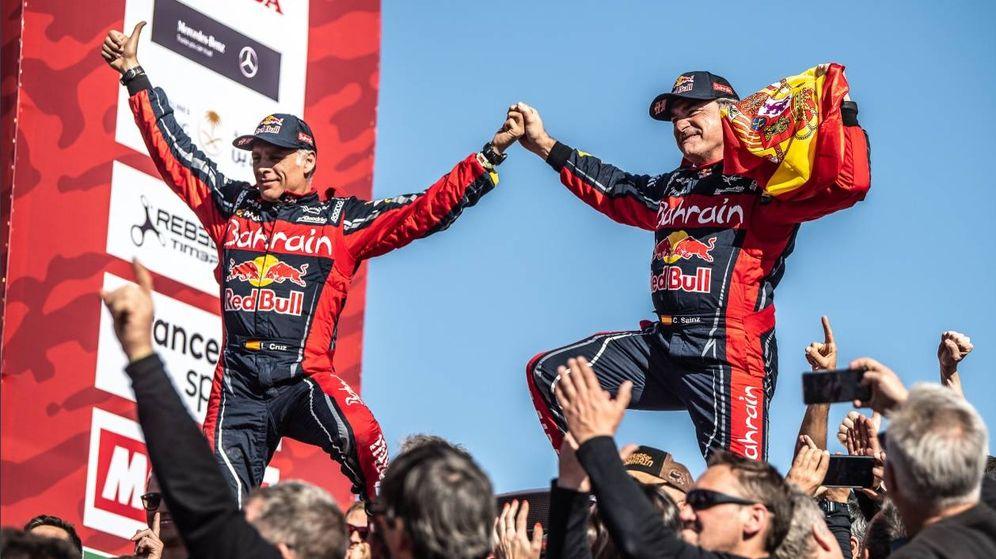 Foto: Lucas Cruz y Carlos Sainz, agarrando con rabia la bandera española, en el podio de Arabia Saudí (X-Raid))