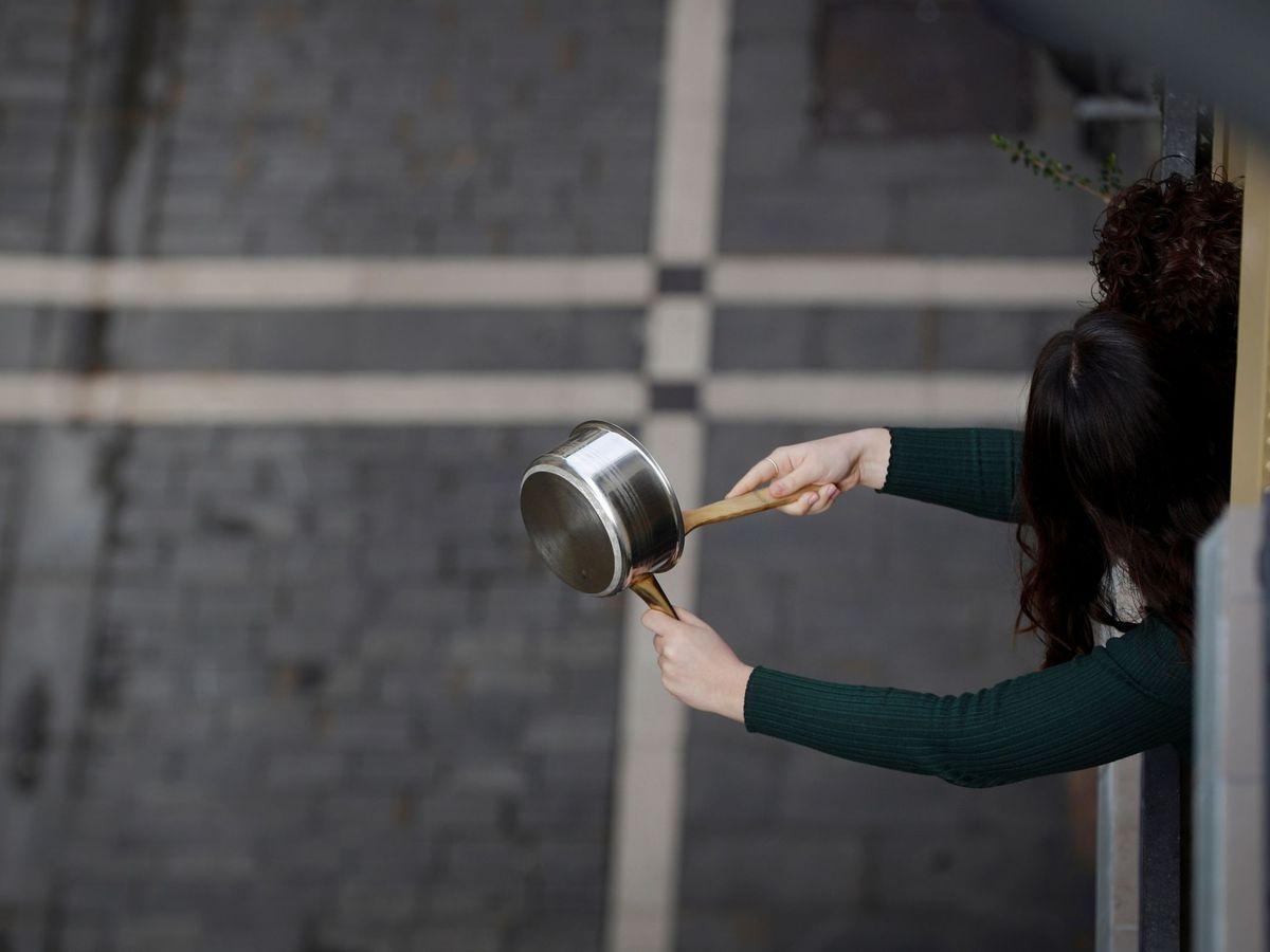 Foto: Una joven hace sonar un cazo desde su balcón en Pamplona. (EFE)