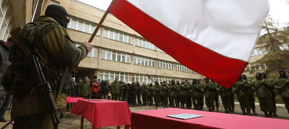 Foto: Un hombre armado, supuestamente un soldado ruso, ondea una bandera de Rusia en Simferópol, capital de Crimea (Reuters).