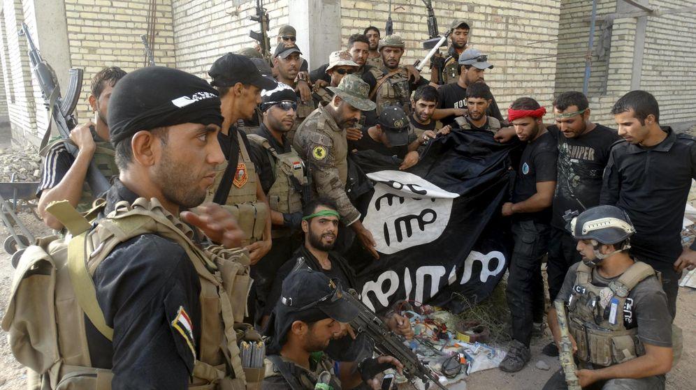 Foto: Miembros de las fuerzas de seguridad iraquíes sostienen una bandera del ISIS capturada en la Universidad de Anbar, en julio de 2015 (Reuters)