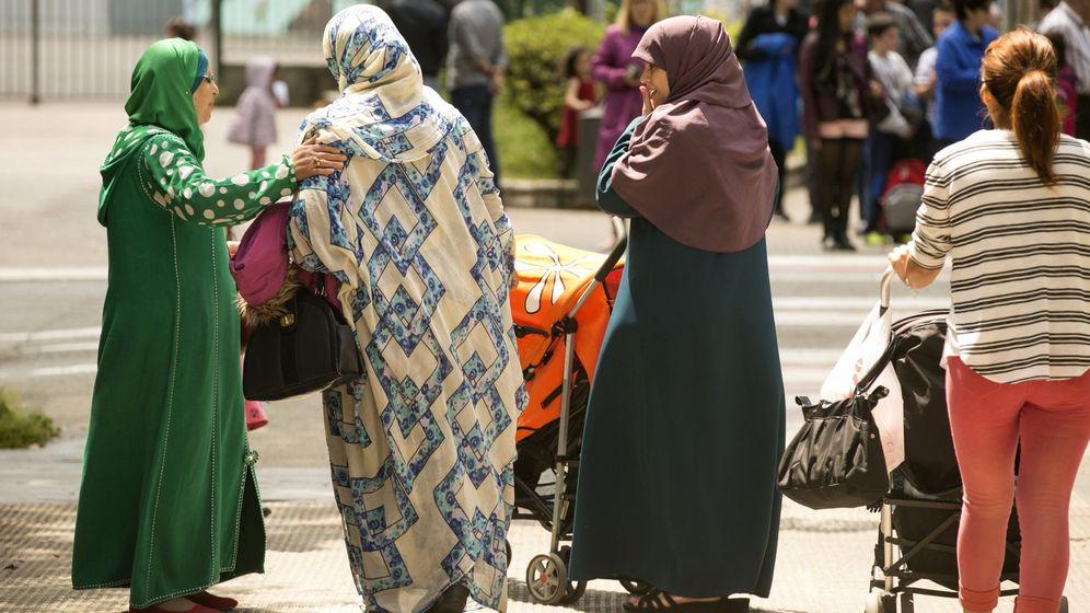 Foto: Madres ataviadas con velo esperan a sus hijos en la puerta de un colegio público. (EFE)