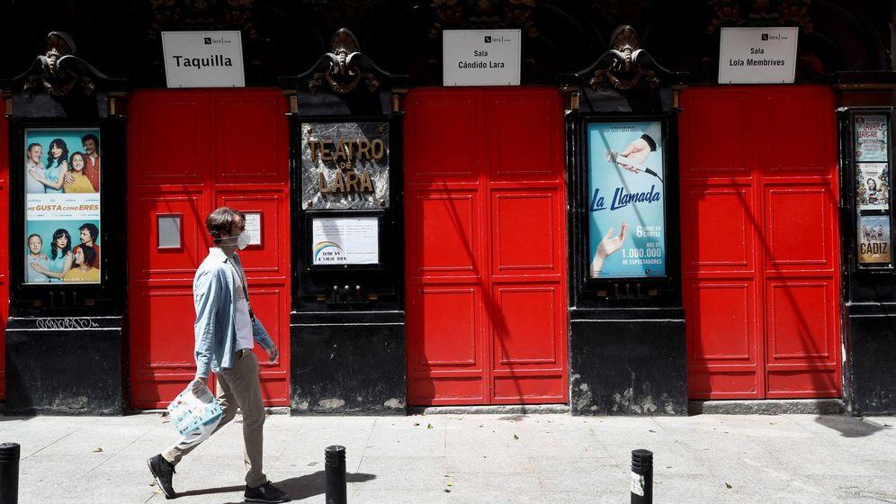 Foto: Un hombre ataviado con una mascarilla sanitaria pasa frente al Teatro Lara del madrileño barrio de Malasaña. (EFE)