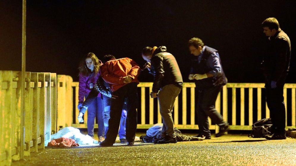 Foto: Efectivos policiales y de los servicios funerarios junto a los cadáveres de las víctimas. (EFE)