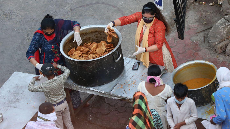Dos mujeres reparten comida en India. (Reuters)