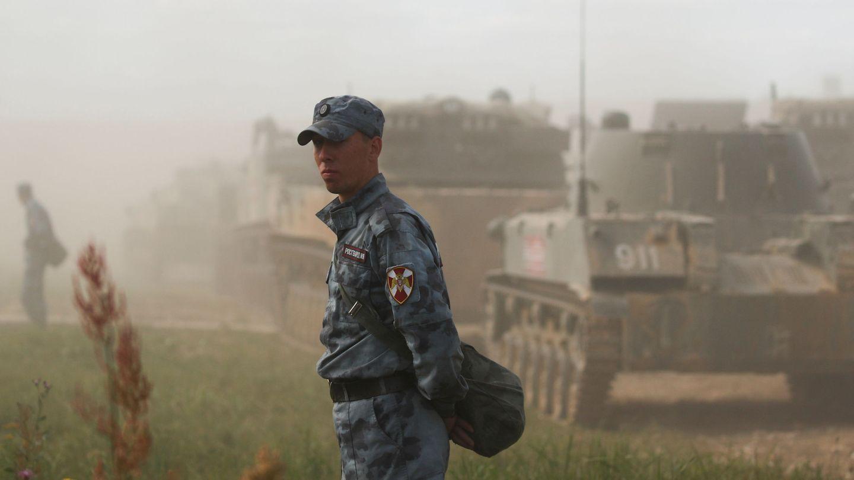 Un oficial de la Russian National Guard ante vehículos blindados durante unas maniobras en Alabino, cerca de Moscú. (Reuters)