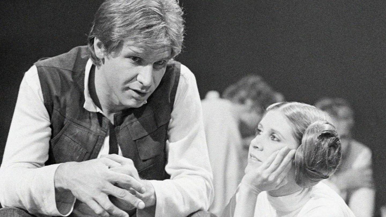 Carrie Fisher mira con devoción a su compañero de pareja y amante Harrison Ford