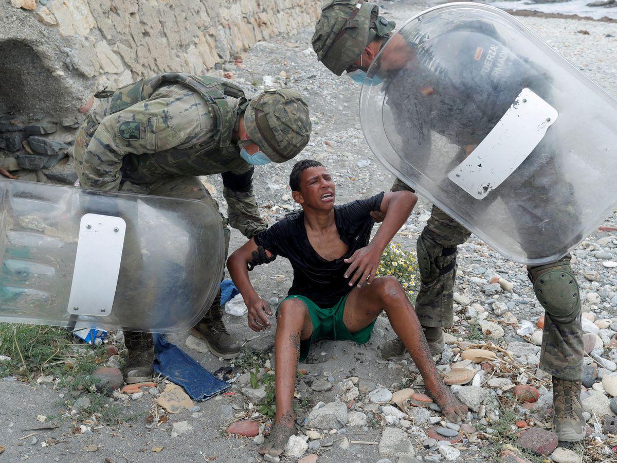 Foto: Soldados levantan a un chico migrante durante la crisis migratoria. (Reuters)