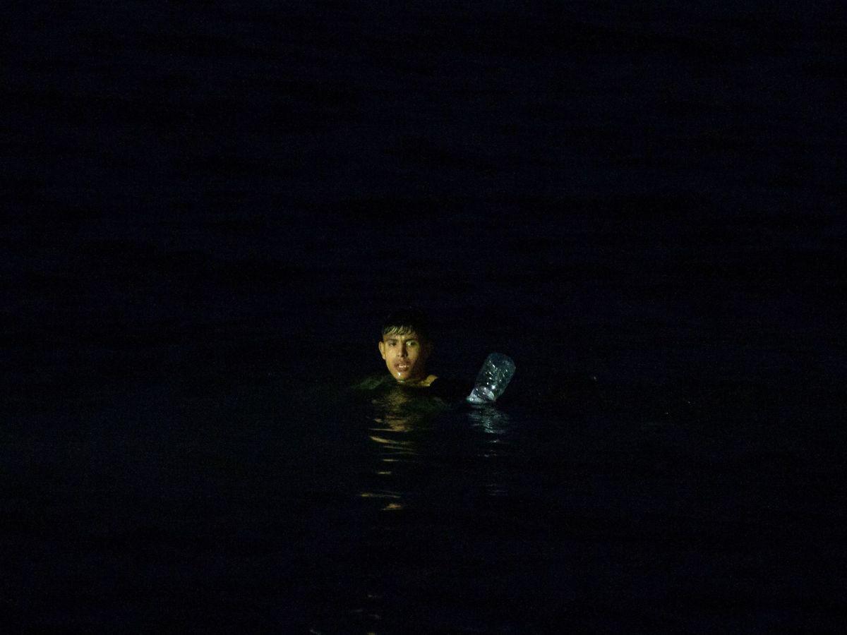 Foto: Un inmigrante intenta cruzar a España por el agua en la playa de El Tarajal. (EFE)