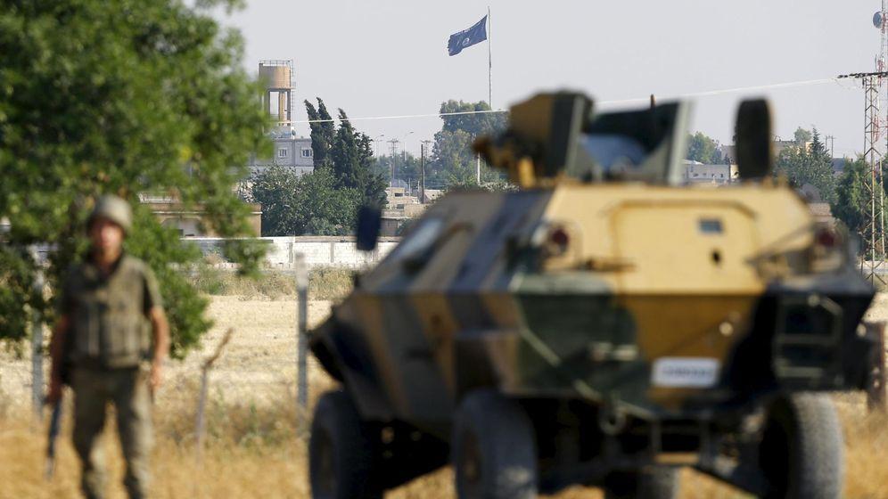 Foto: Un blindado turco custodia el paso fronterizo entre Akçakale (Turquía) y Tel Abyad (Siria). Al fondo ondea una bandera del Estado Islámico (Reuters)