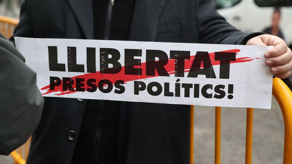 Foto: Un hombre sostiene un cartel con el lema 'Libertat presos polítics' a las puertas del Tribunal Supremo. (EFE)