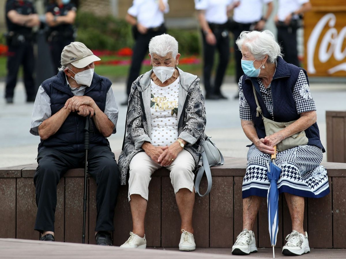 Foto: Unos ancianos conversan protegidos con mascarillas en San Sebastián. (EFE)